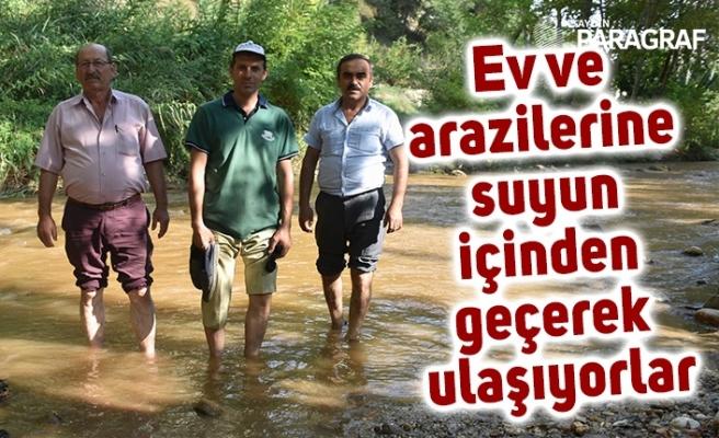 Ev ve arazilerine suyun içinden geçerek ulaşıyorlar