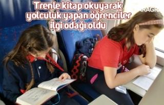 Trenle kitap okuyarak yolculuk yapan öğrenciler...